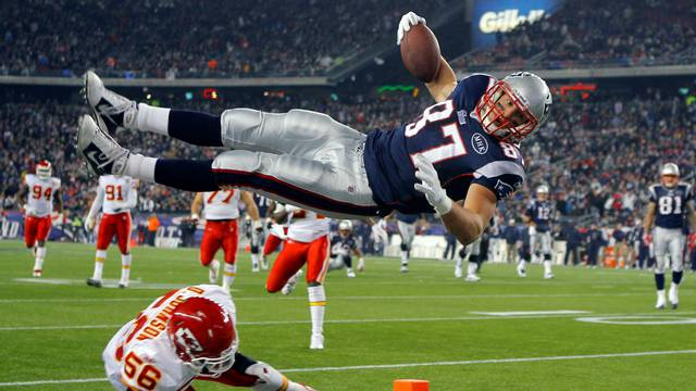 FILE PHOTO: New England Patriots tight end Rob Gronkowski (top) scores a touchdown over Kansas City Chiefs linebacker Derrick Johnson in the second half of their NFL football game in Foxborough