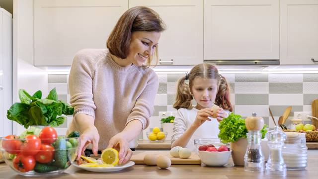 Smiling mother and daughter 8, 9 years old cooking together in kitchen vegetable salad. Healthy home food, communication parent and child.
