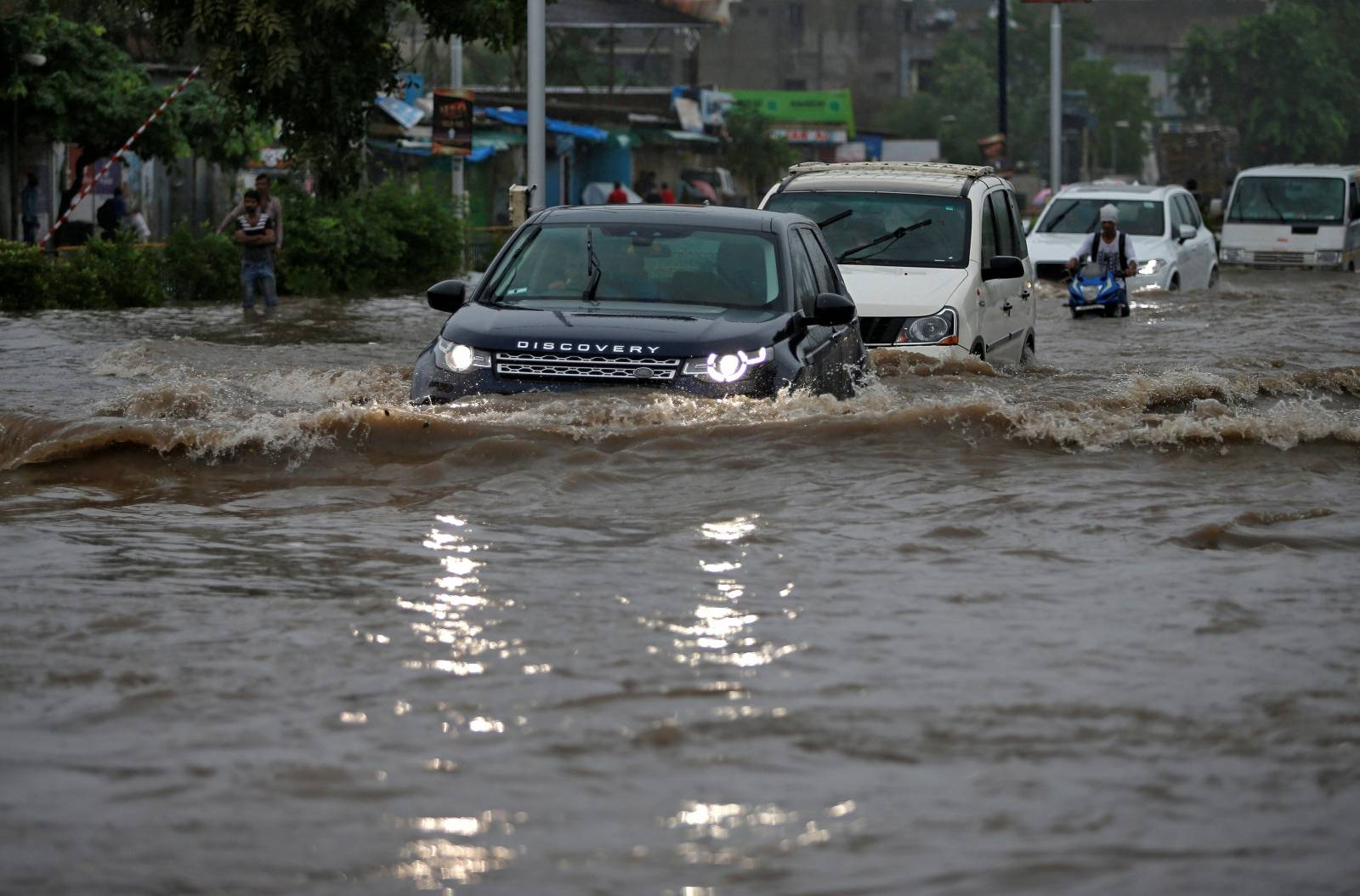 Vehicles move through a water-logged road after heavy rains in Ahmedabad