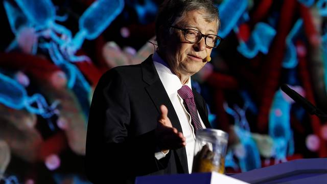 Microsoft founder Bill Gates points at a jar containing human faeces during his speech at the Reinvented Toilet Expo showcasing sewerless sanitation technology in Beijing