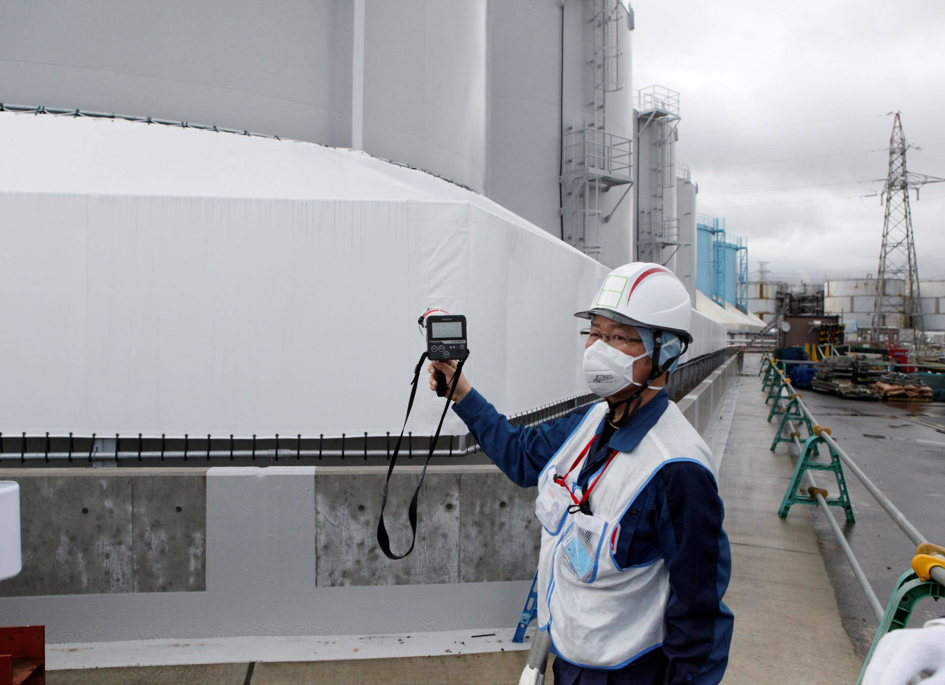 FILE PHOTO: A Tokyo Electric Power Co (TEPCO) employee uses a geiger counter at the company's tsunami-crippled Fukushima nuclear plant