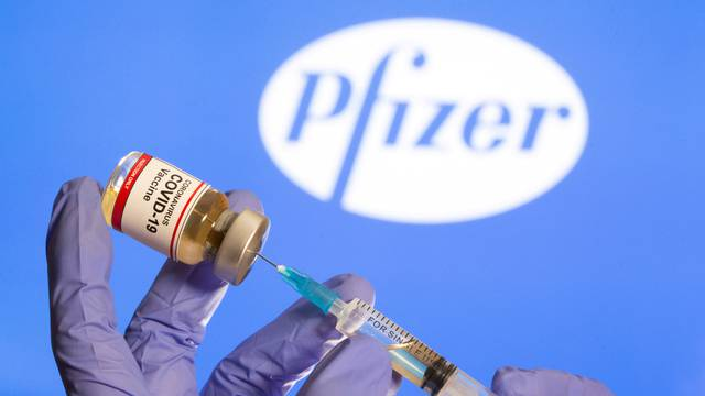 """FILE PHOTO: FILE PHOTO: FILE PHOTO: A woman holds a small bottle labeled with a """"Coronavirus COVID-19 Vaccine"""" sticker and a medical syringe in front of displayed Pfizer logo in this illustration"""