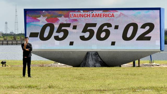 A reporter does a stand-up in front of the countdown clock  the press site before the launch of the SpaceX Crew Dragon on a Falcon 9 booster rocket from Pad39A