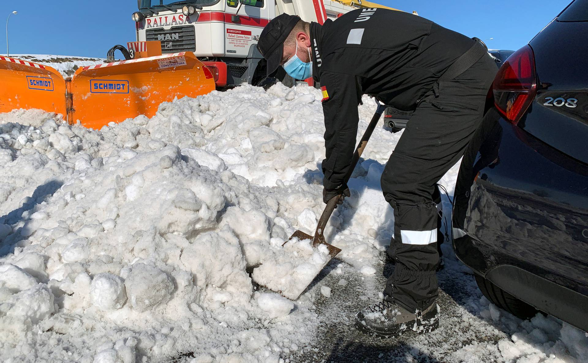 A member of Spain's military unit (UME) shovels snow next to cars accumulated on M-40 highway after heavy snowfall in Madrid