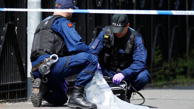 Police officers search a Nike bag in Hulme, Manchester
