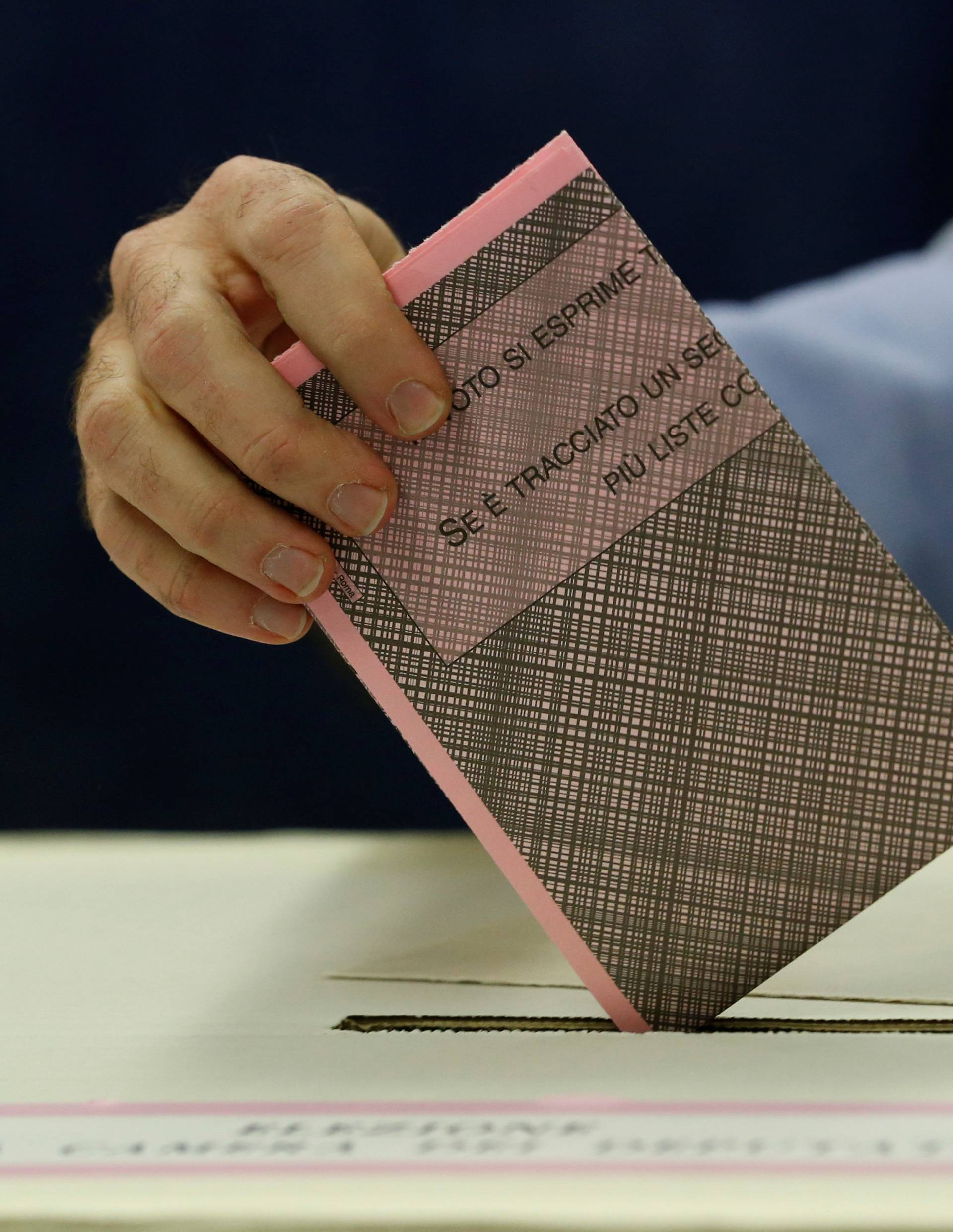 A man casts his vote at a polling station in Milan
