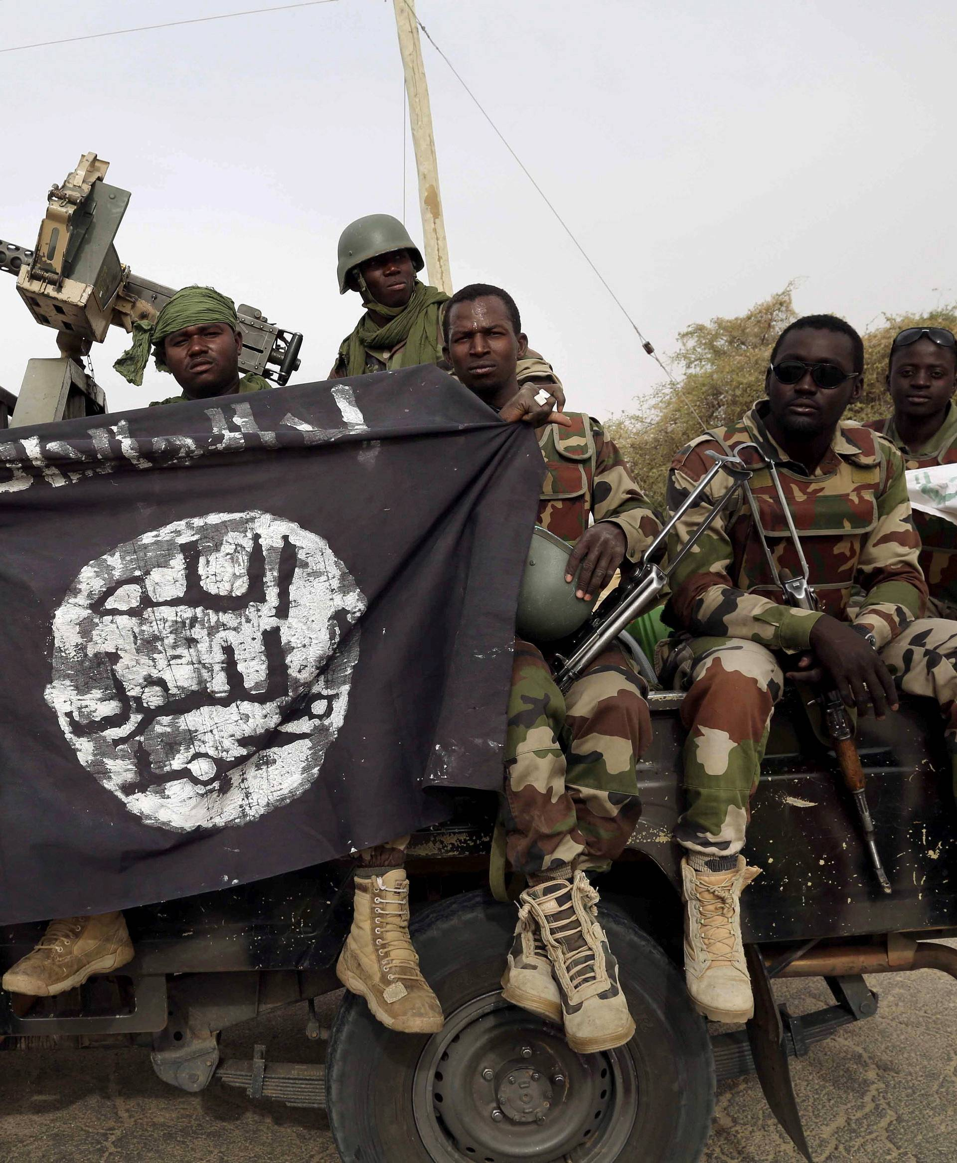 FILE PHOTO: Nigerian soldiers hold up a Boko Haram flag that they had seized in the recently retaken town of Damasak, Nigeria