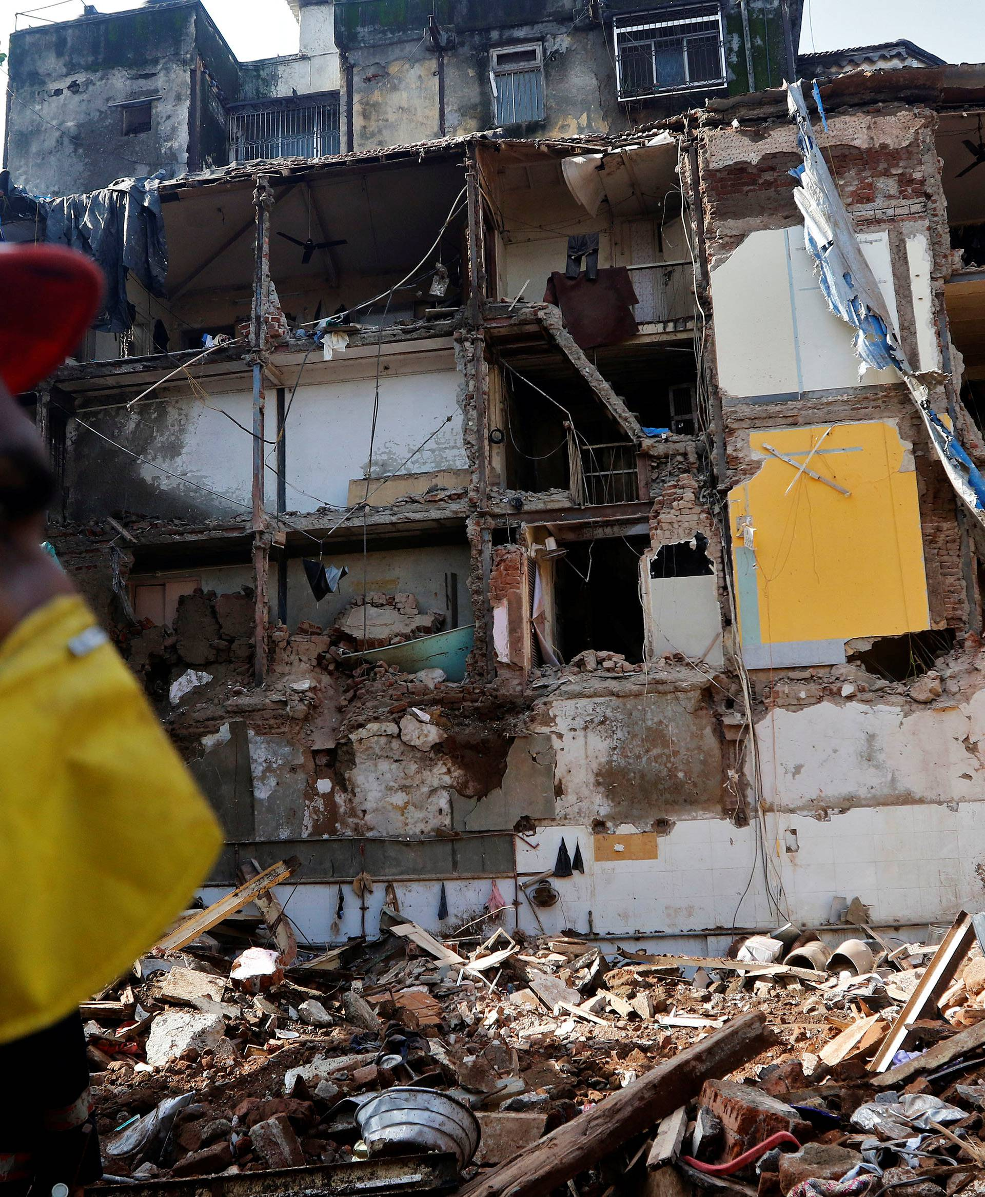 A rescue worker searches for survivors at the site of a collapsed building in Mumbai