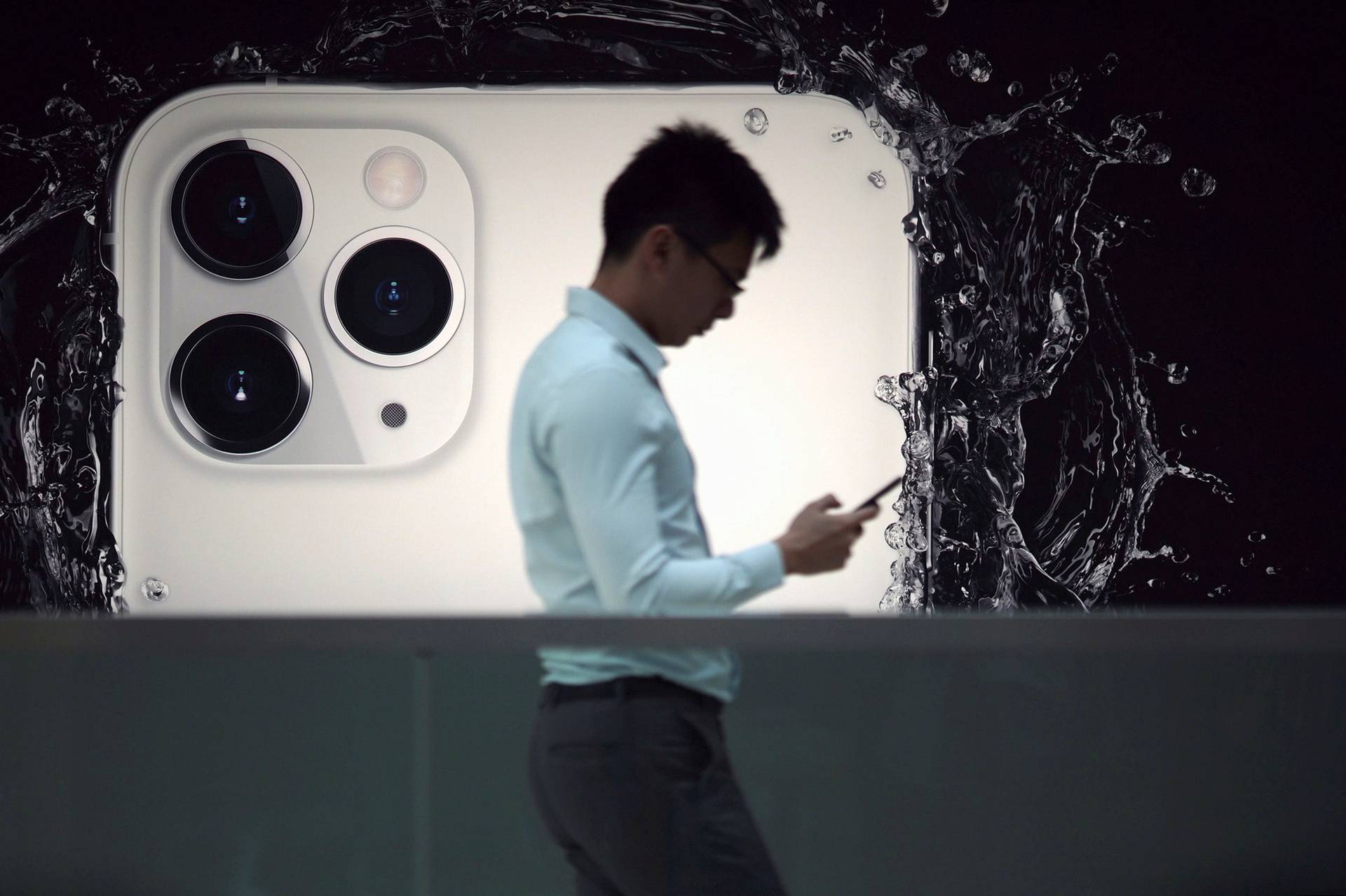 FILE PHOTO: A man walks next to an advertisement for Apple's new iPhone 11 Pro at the Apple Store in IFC, Central district, Hong Kong, China
