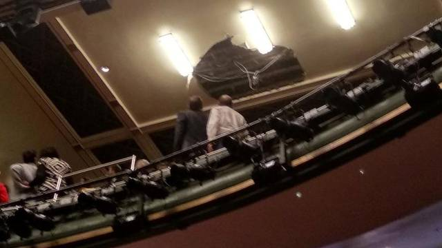 People look at the collapsed roof of Piccadilly Theatre during 'Death of a Salesman' play in London