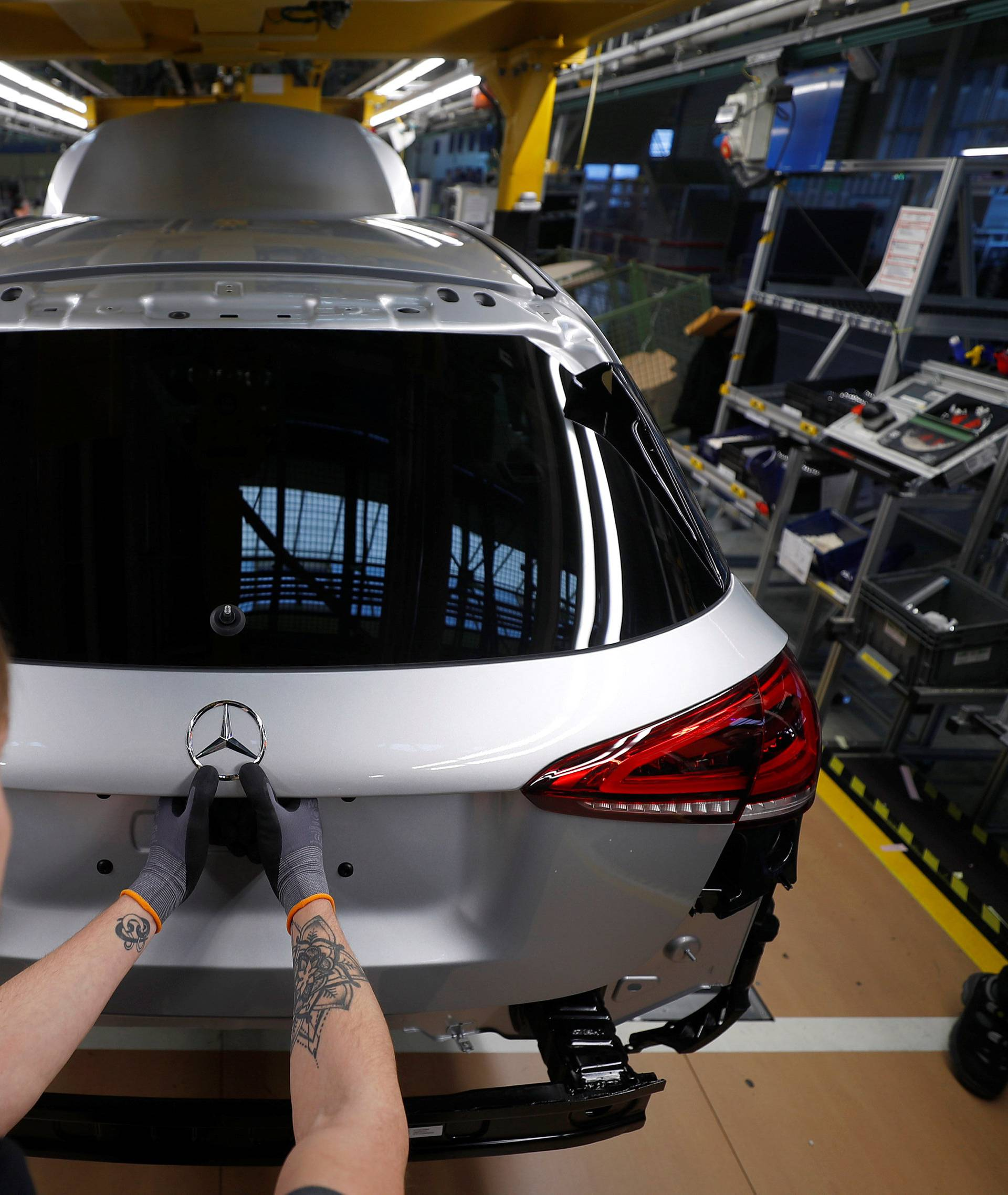 "An employee of German car manufacturer Mercedes Benz installs the characteristic ""Mercedes star"" at a A-class model at the production line at the Daimler factory in Rastatt"