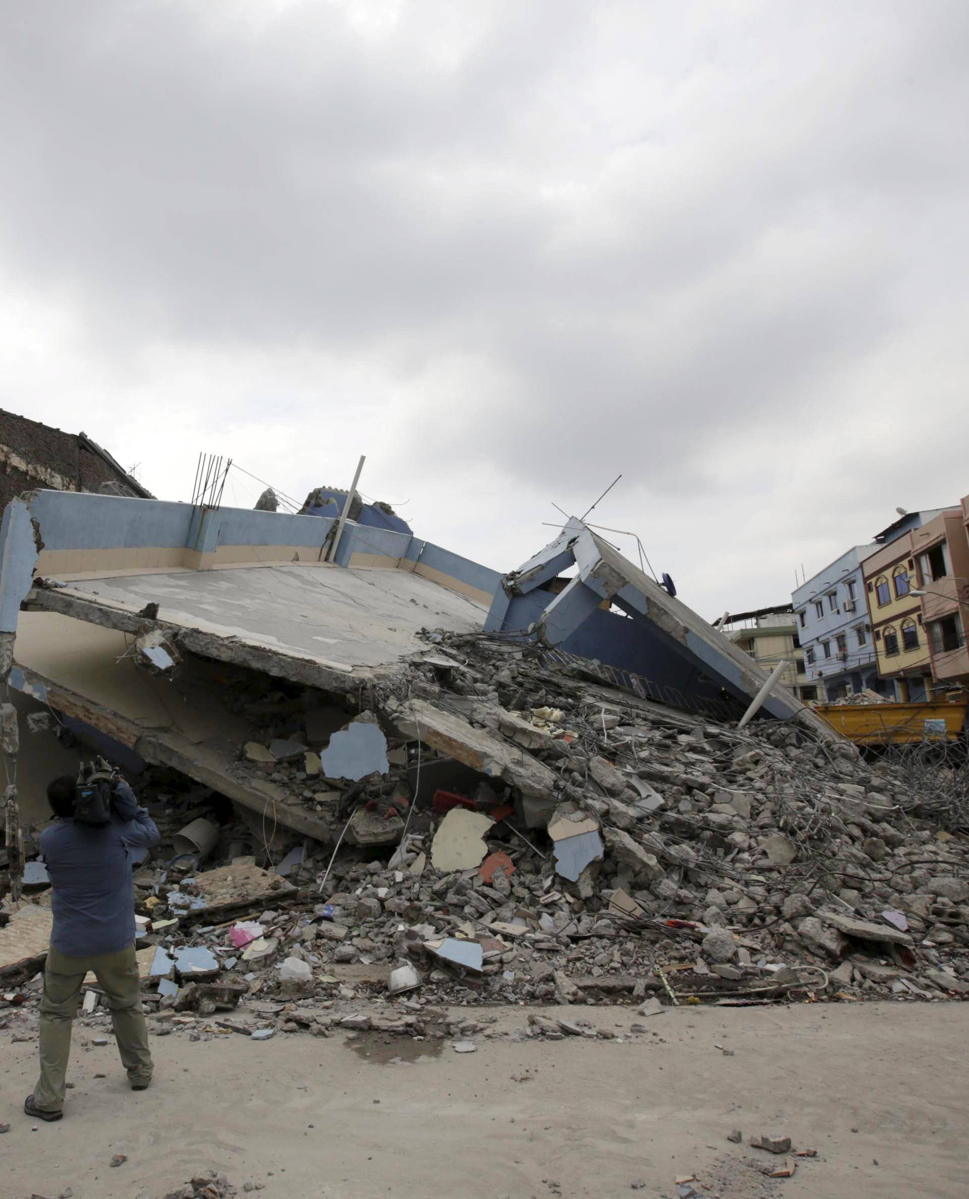 A television cameraman films a collapsed building in Guayaquil after an earthquake struck off the Pacific coast in Ecuador