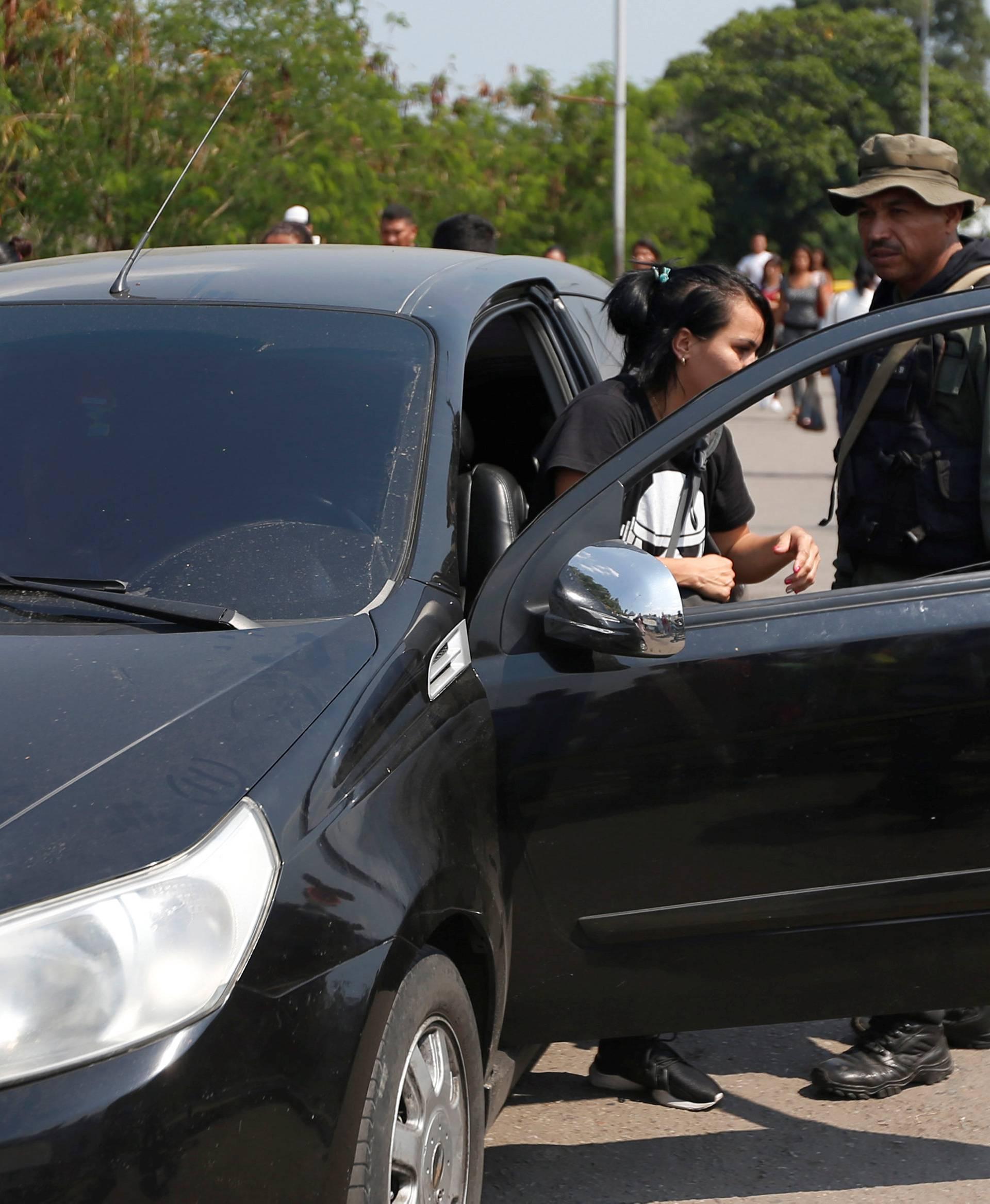 A woman gets out of her car at the request of a Venezuelan guard, on the Francisco de Paula Santander international bridge in Cucuta