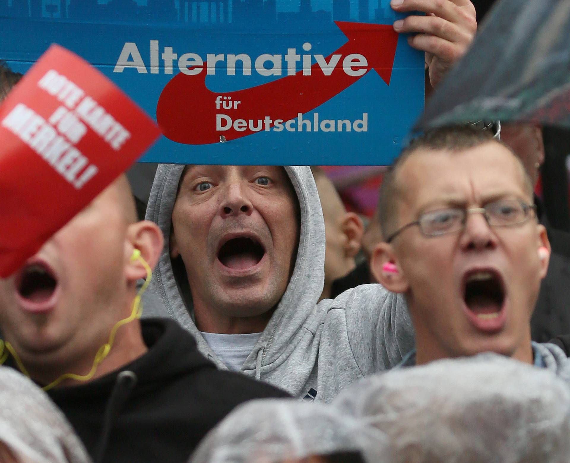 Supporters of the hard-right Alternative for Germany (AfD) party shout slogans durig an election campaign rally of German Chancellor Angela Merkel in Torgau