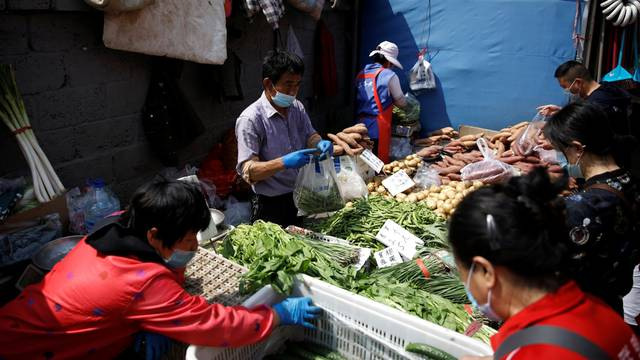 A vegetable stall vendor wearing a face mask attends to customers at an outdoor market in Beijing, following the novel coronavirus disease (COVID-19) outbreak