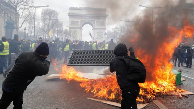 """Protesters react next to a burning barricade during a demonstration by the """"yellow vests"""" movement in Paris"""