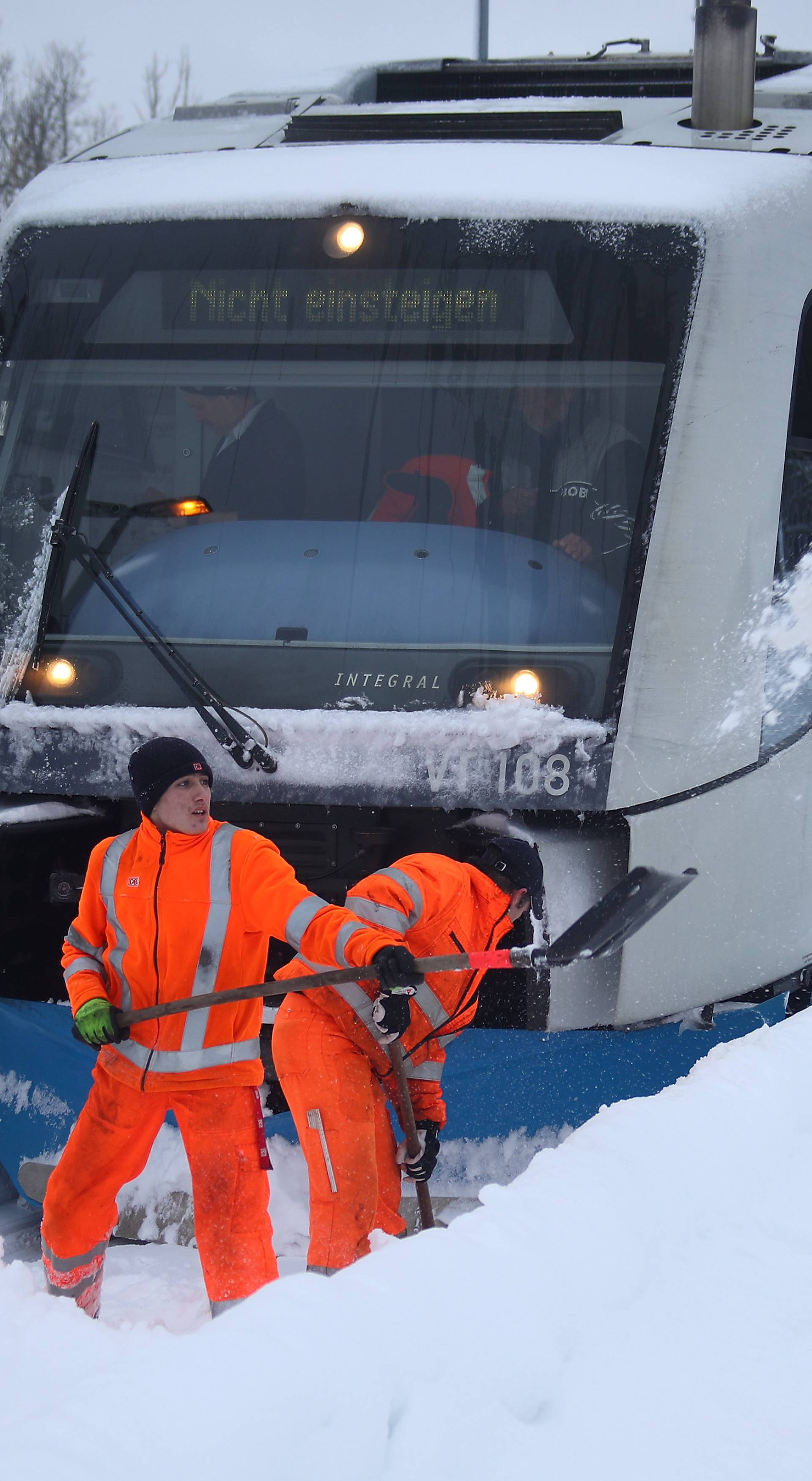 Workers try to clear rail tracks after heavy snowfalls in Schaftlach