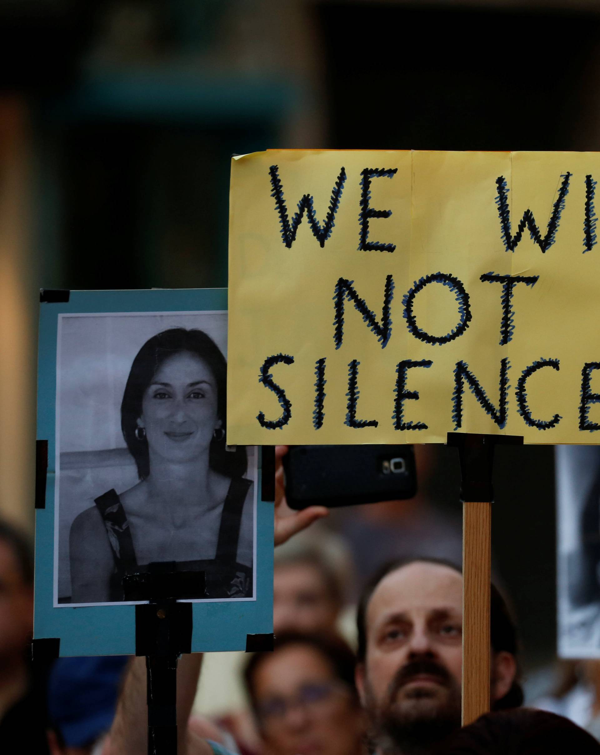 People hold photos of assassinated anti-corruption journalist Daphne Caruana Galizia during a vigil to mark eleven months since her murder in a car bomb in Valletta