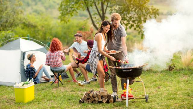 Young,Female,And,Male,Couple,Baking,Barbecue,In,Nature