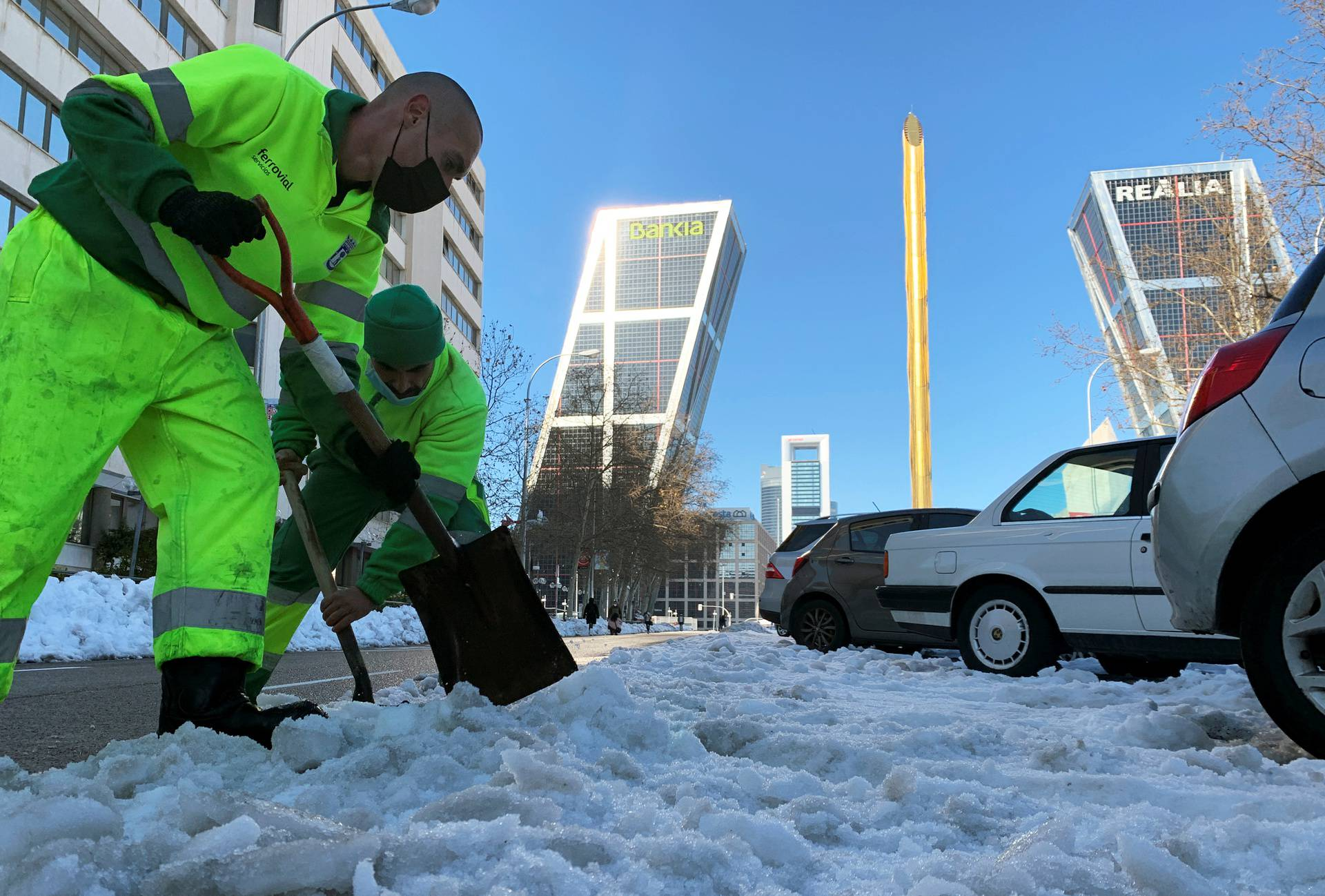 Workers shovel snow in front of headquarters of Spanish lenders Bankia after heavy snowfall in Madrid