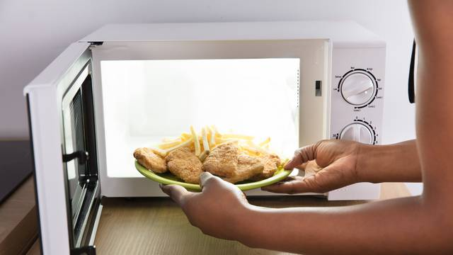Person Heating Fried Food In Microwave Oven