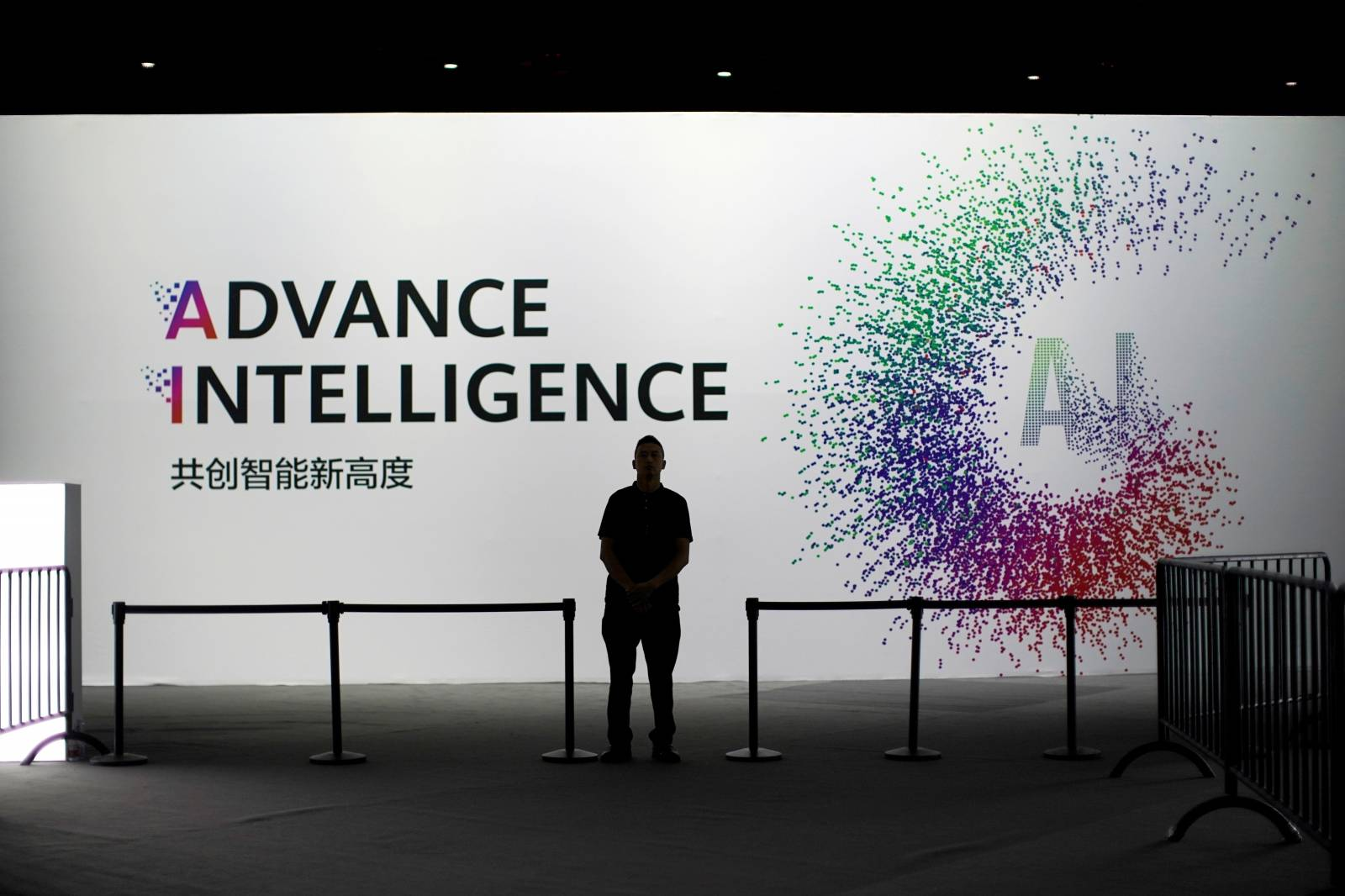 FILE PHOTO: A security officer keeps watch in front of an AI (Artificial Intelligence) sign at the annual Huawei Connect event in Shanghai