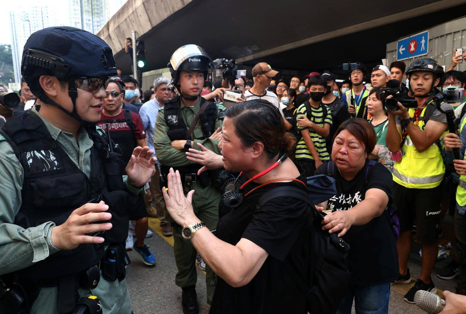 An anti-government protester argues with a riot police officer near Amoy Plaza shopping mall in Kowloon Bay, Hong Kong