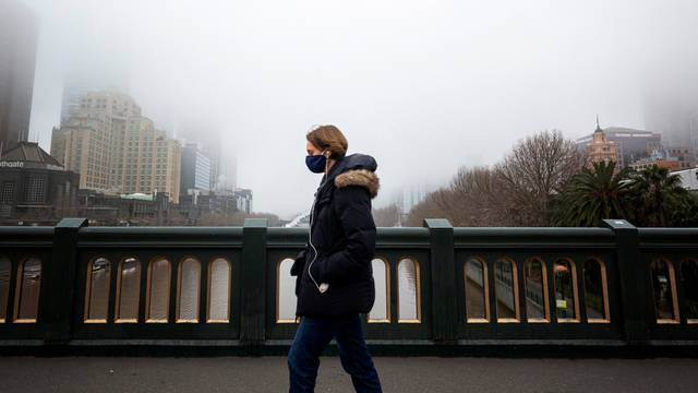 A person in a protective face mask walks along the Princes Bridge in Melbourne