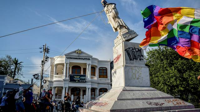 Demonstrators tear down a statue of Cristobal Colon, also known as Christopher Columbus, during protests, in Barranquilla