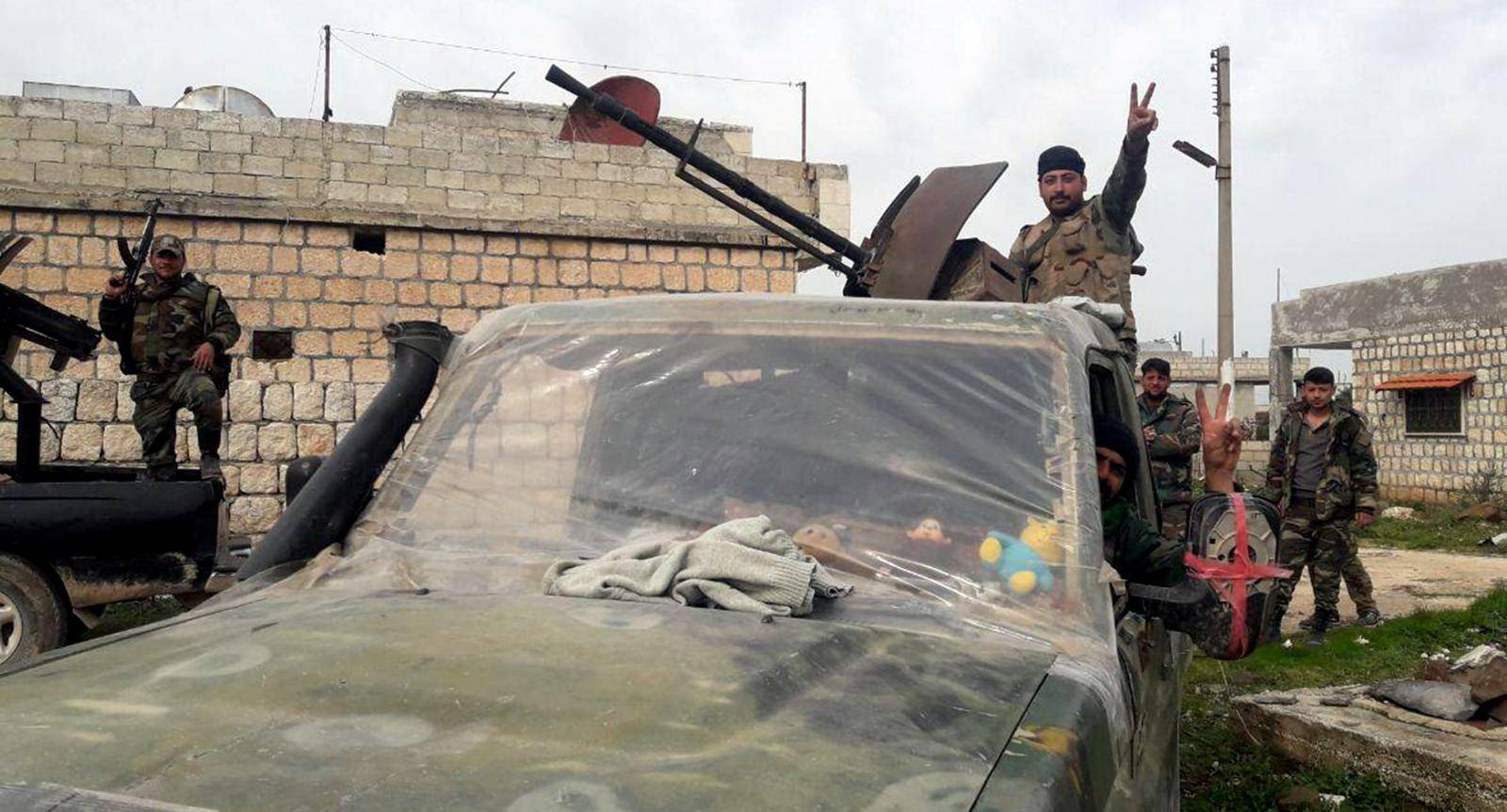 Syrian army soldiers gesture in southern Idlib province