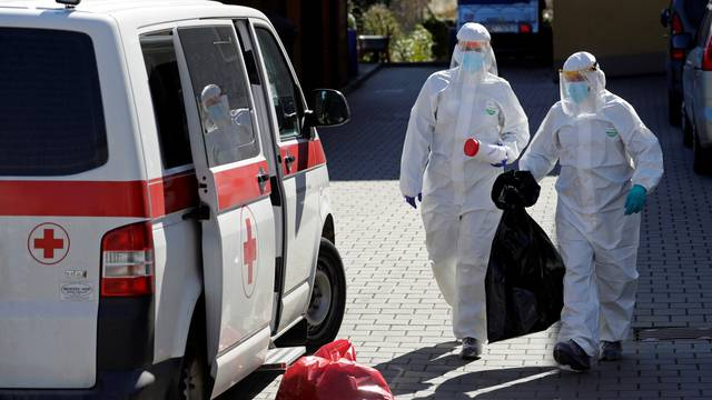 Members of Czech Army wearing protective gear carry samples in Brno