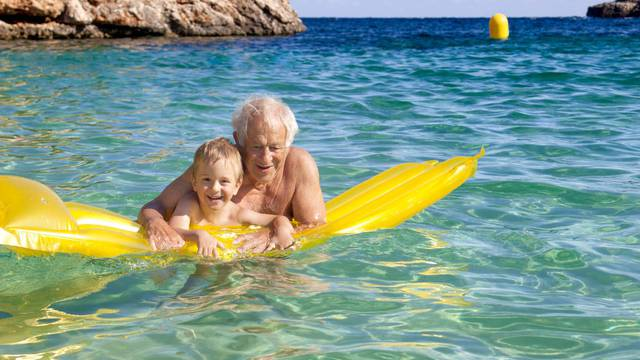 Senior Man And Grandson having fun On Inflatable Air Bed