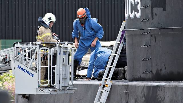 "Police technicians investigate the rescued private submarine ""UC3 Nautilus"" in Copenhagen Harbor"