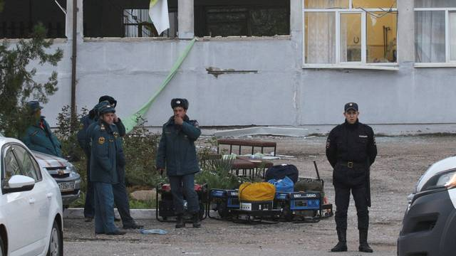 A Russian policeman and Emergencies Ministry members gather outside the damaged building of a college following a recent attack in Kerch