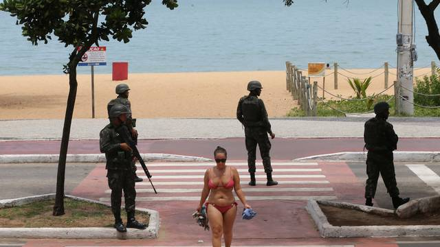 A woman walks as army soldiers patrol at Costa beach in Vitoria