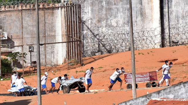 Inmates transport bodies after a prison riot in Natal