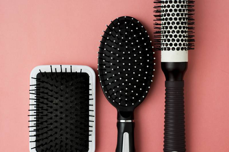 Used Hair brush tools on pink or coral background with copy space. Beauty fashion, hair care background.