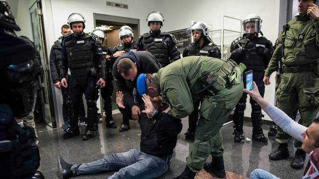 A man is removed after protesters briefly broke into Serbia's state television building during a protest against Serbian President Aleksandar Vucic and his government in central Belgrade