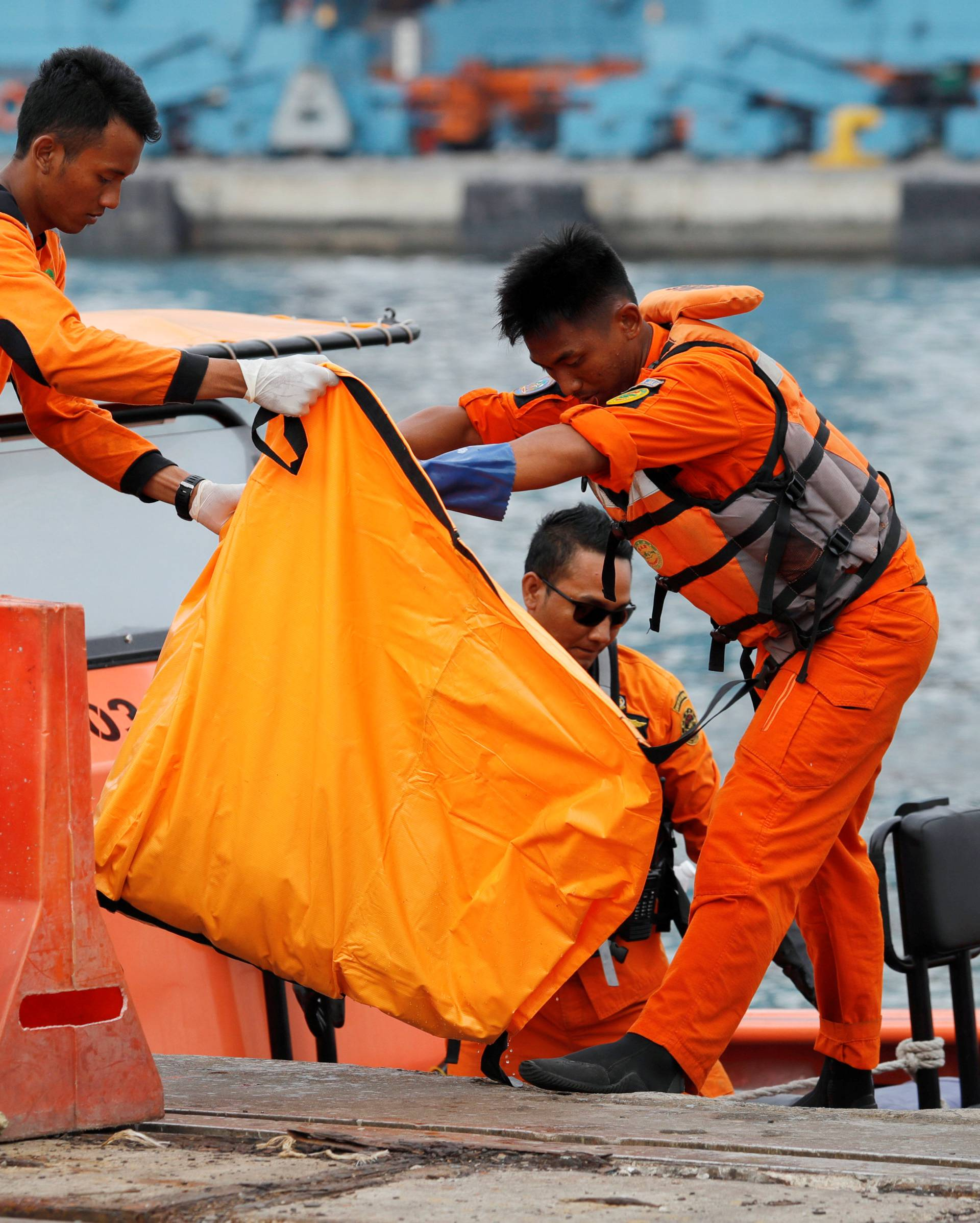 Rescue team members carry a bag containing the body of a passenger from the Lion Air flight JT610 at Tanjung Priok port in Jakarta