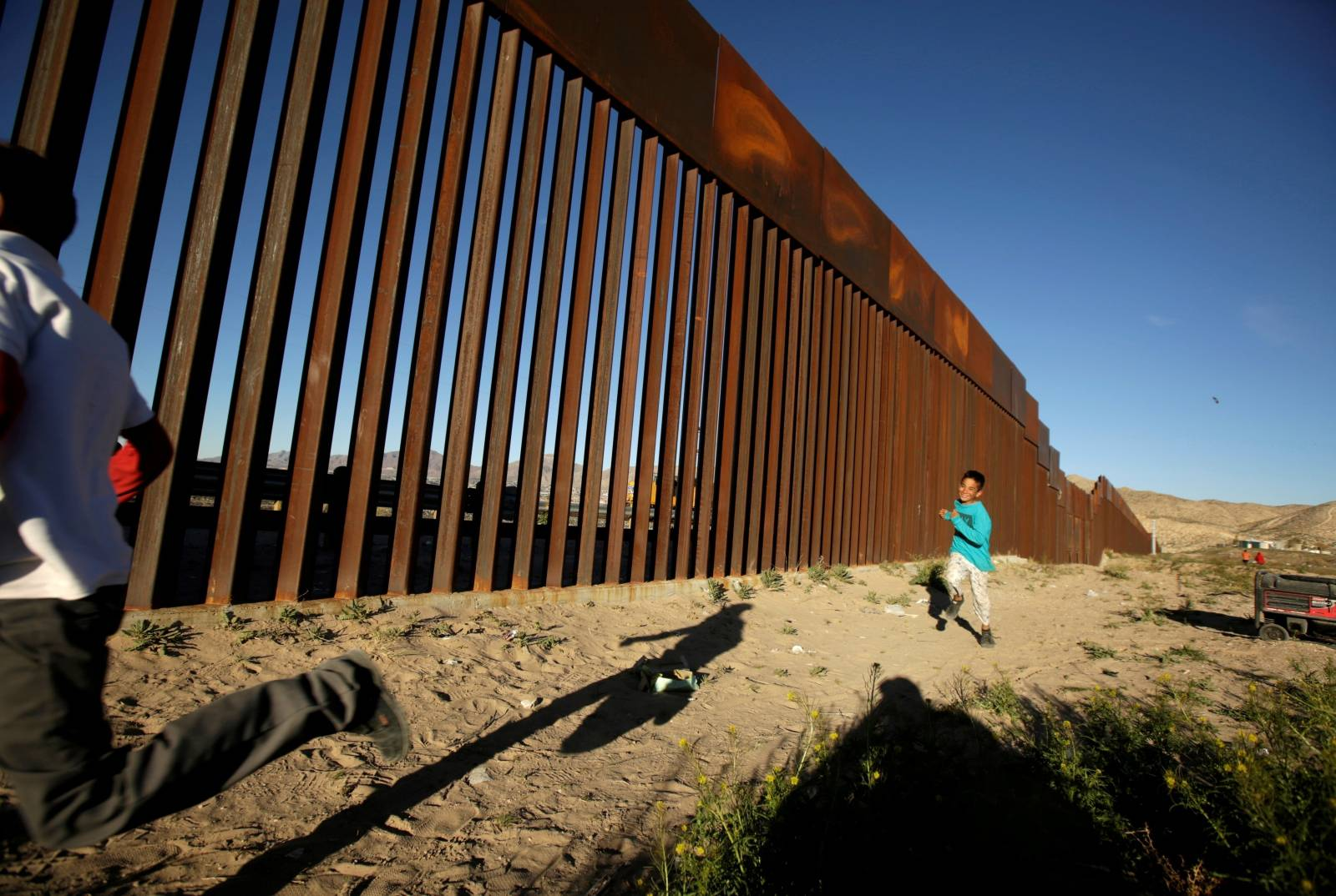 FILE PHOTO: Children run along the border fence between Mexico and the United States during an inter-religious service against U.S. President Donald Trump's border wall, in Ciudad Juarez