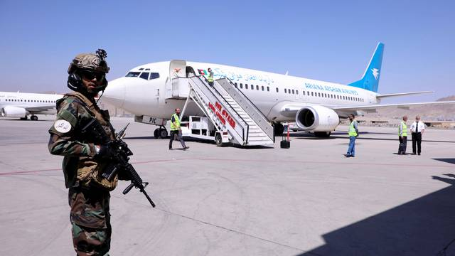 A member of Taliban forces stands guard next to a plane at Hamid Karzai International Airport in Kabul