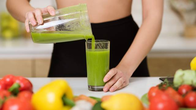 Healthy eating. Woman pouring detox shake to glass