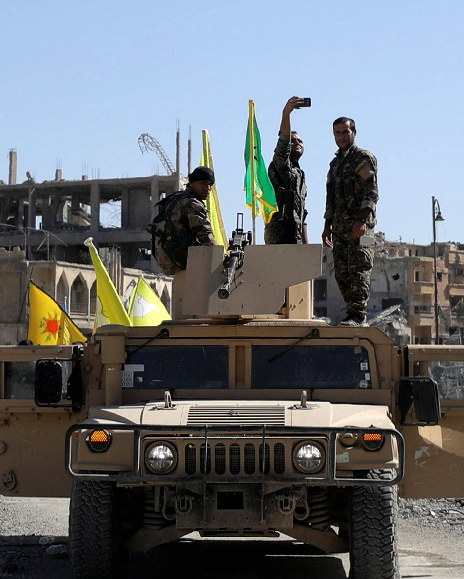 A Fighter of Syrian Democratic Forces takes a selfie as he stands on a military vehicle in Raqqa