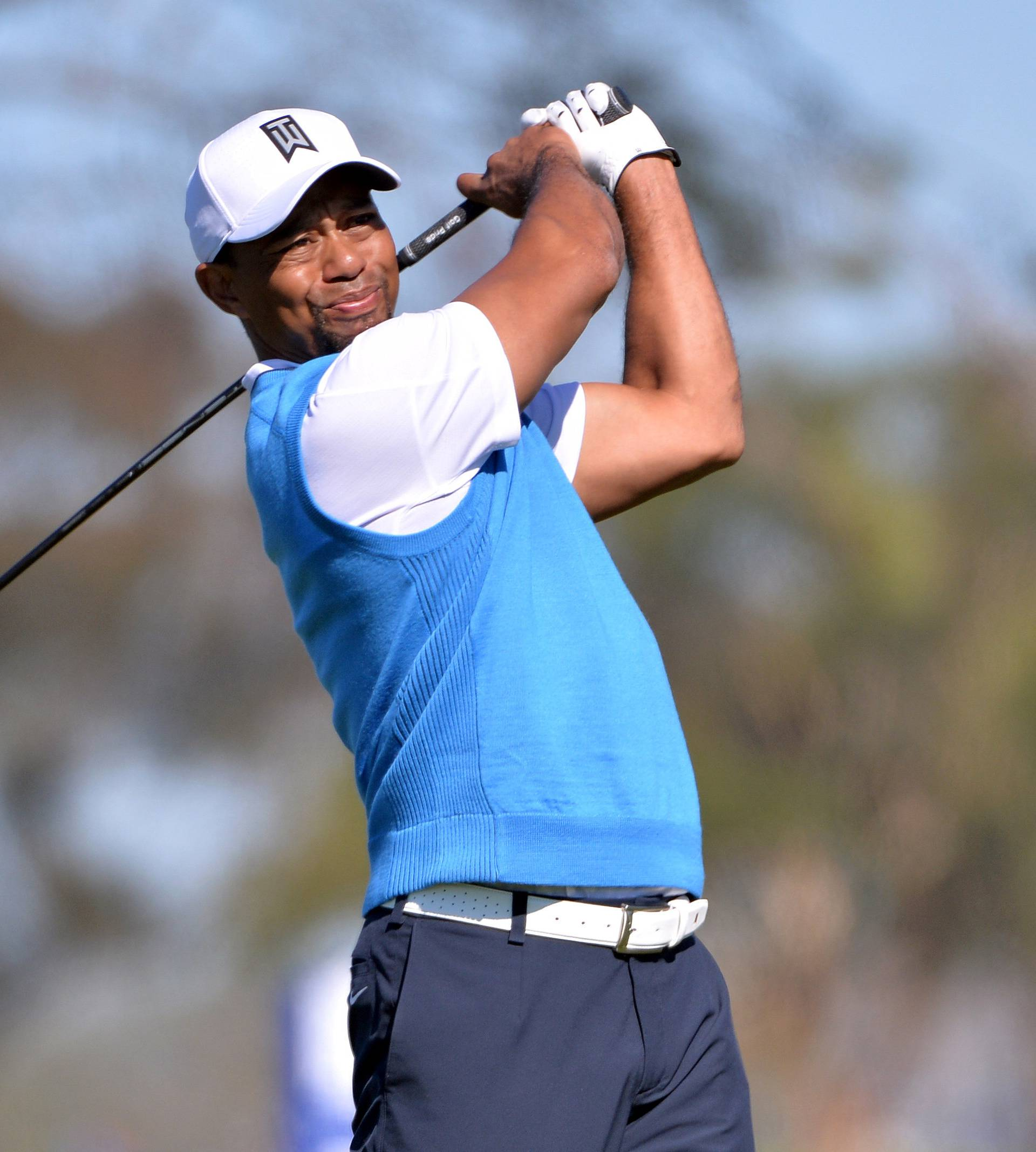 FILE PHOTO: Tiger Woods tees off the 5th hole during the first round of the Farmers Insurance Open golf tournament in La Jolla