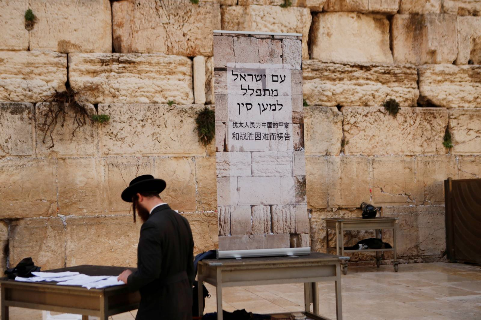 A Jewish worshipper prays next to a placard at the Western Wall in Jerusalem's Old City