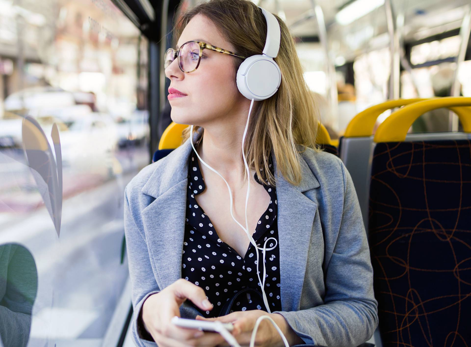 Pretty young woman listening to music with mobile phone at the bus.