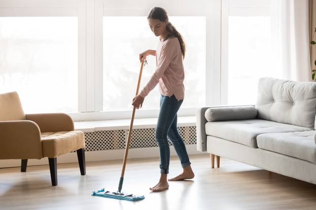 Barefoot girl doing house cleaning using microfiber wet mop pad