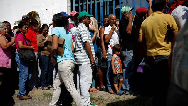 Zulay Pulgar, stands in line outside a hardware store, next to her son Emmanuel, to buy cement and resell it in Punto Fijo