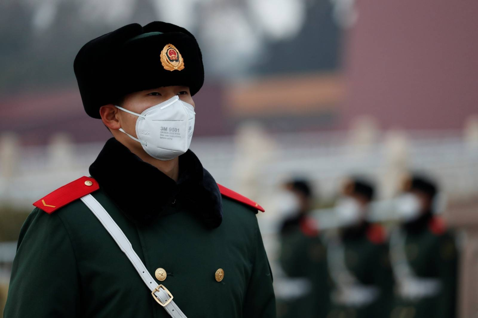 A paramilitary officer wearing a face masks stands guard at the Tiananmen Gate, as the country is hit by an outbreak of the new coronavirus, in Beijing