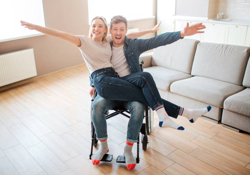 Young man with disability and inclusiveness holding girlfirend on knees. They smile and pose on camera. Cheerful happy couple.